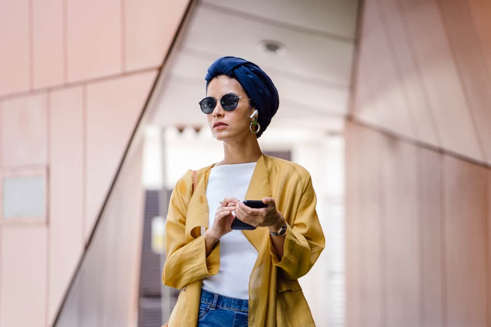 Woman in a modest style outfit listening to music via wireless earphones.