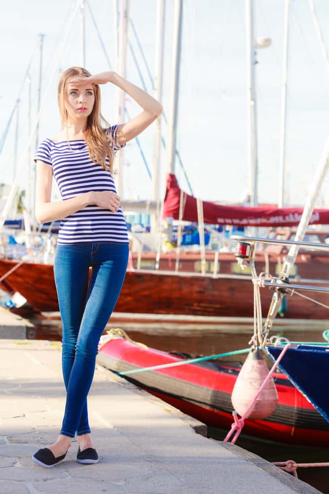 Girl in a striped shirt and denim pants standing near yachts.