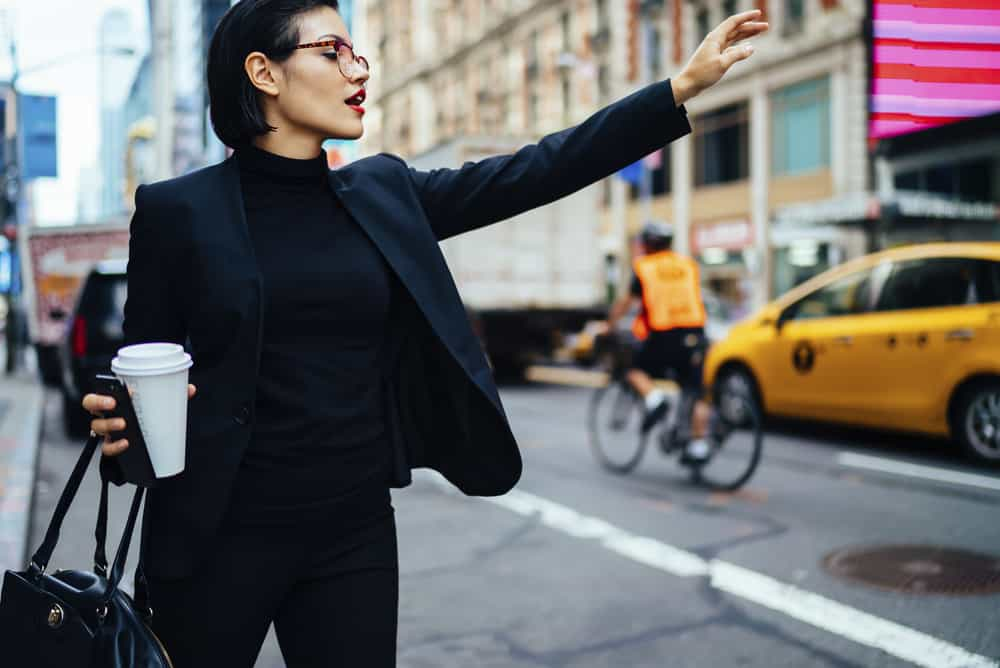 Woman in an NYC style outfit calling a cab.