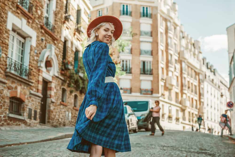 Woman in a blue checkered dress with belt and hat walking along the street of Paris.
