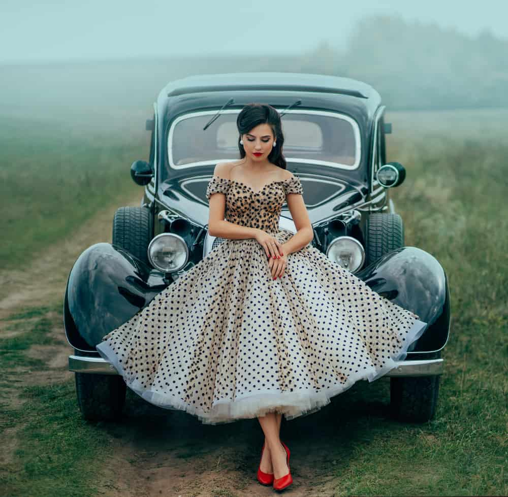 Model in pin up style clothes posing against a black retro car.