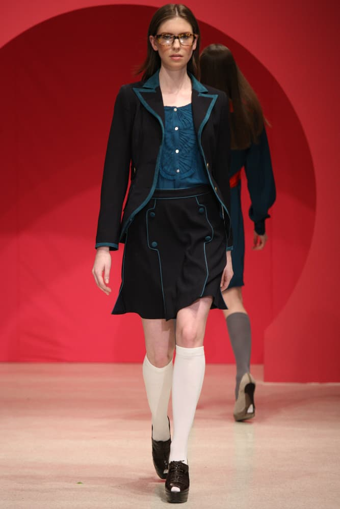 Model in preppy clothes walks the runway.
