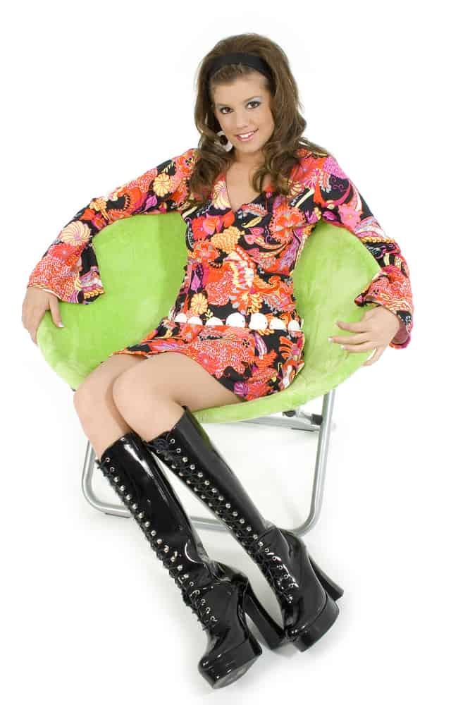 Woman in a psychedelic dress and boots sitting on a green round chair.