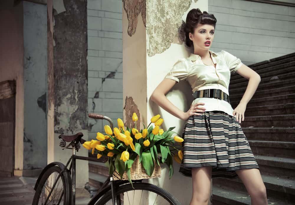 Retro lady posing against a pillar next to a bike.
