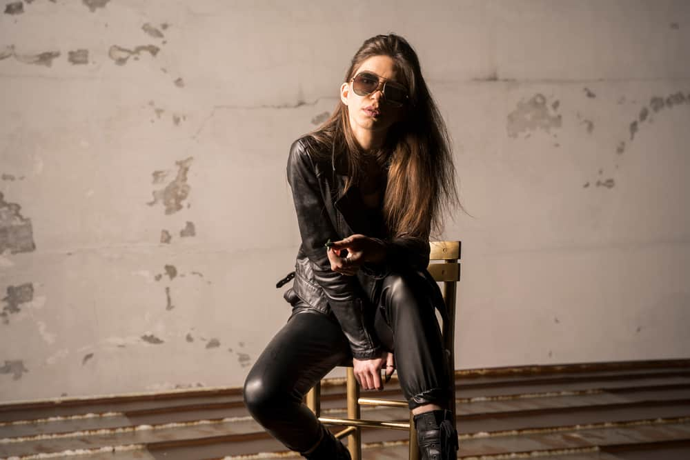 Rocker chic wearing leather jacket and pants sitting in an abandoned room.