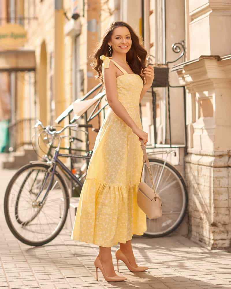 Woman in a yellow sundress walking on the street.