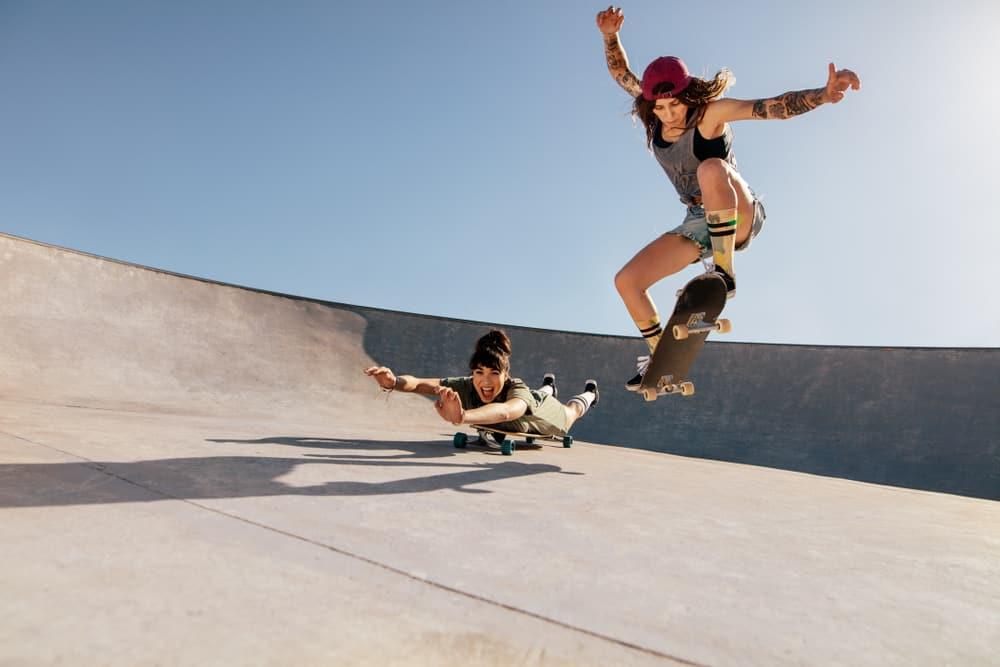 Two women doing stunts on skateboards at a skate park.