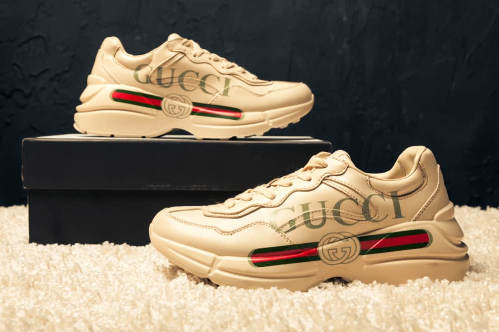 This is a close look at a pair of Gucci sneakers on display.
