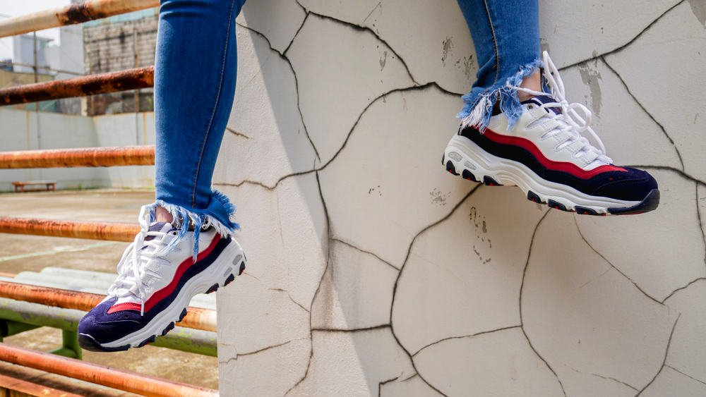 This is a close look at a man wearing a pair of Skecher sneakers with his ripped jeans.