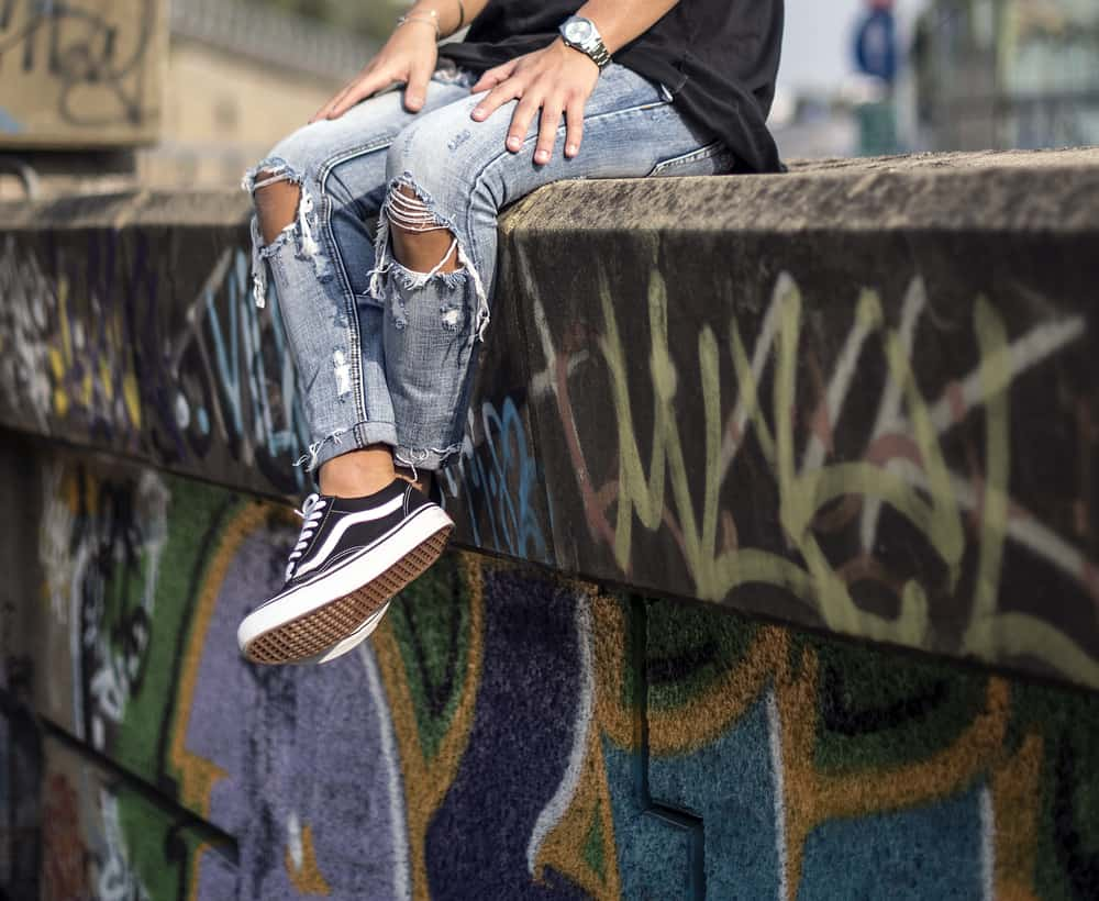 A man wearing a pair of Vans sneakers with his ripped jeans.