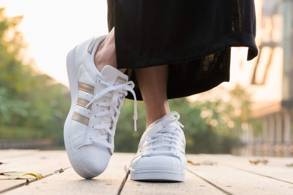 This is a close look at a woman wearing a pair of white Adidas sneakers.