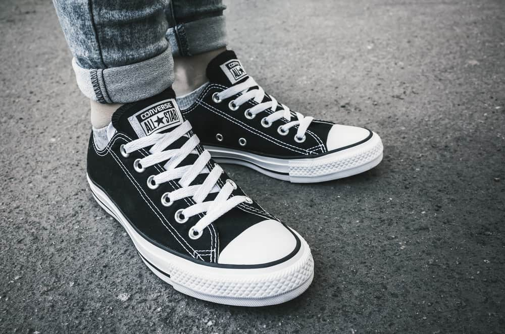 This is a close look at a woman wearing a pair of black Converse sneakers.