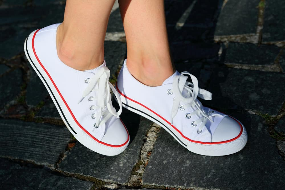 A close look at a woman wearing a pair of white Keds sneakers.