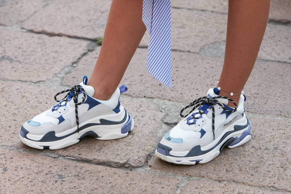A woman wearing a pair of Balenciaga sneakers.