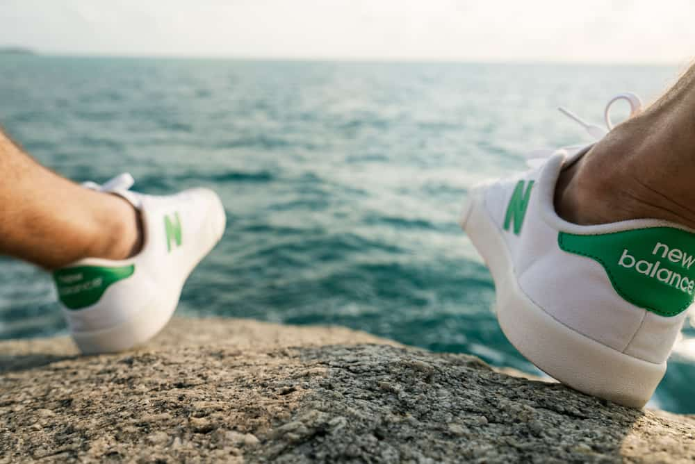 This is a close look at a man wearing a pair of New Balance sneakers by the sea.