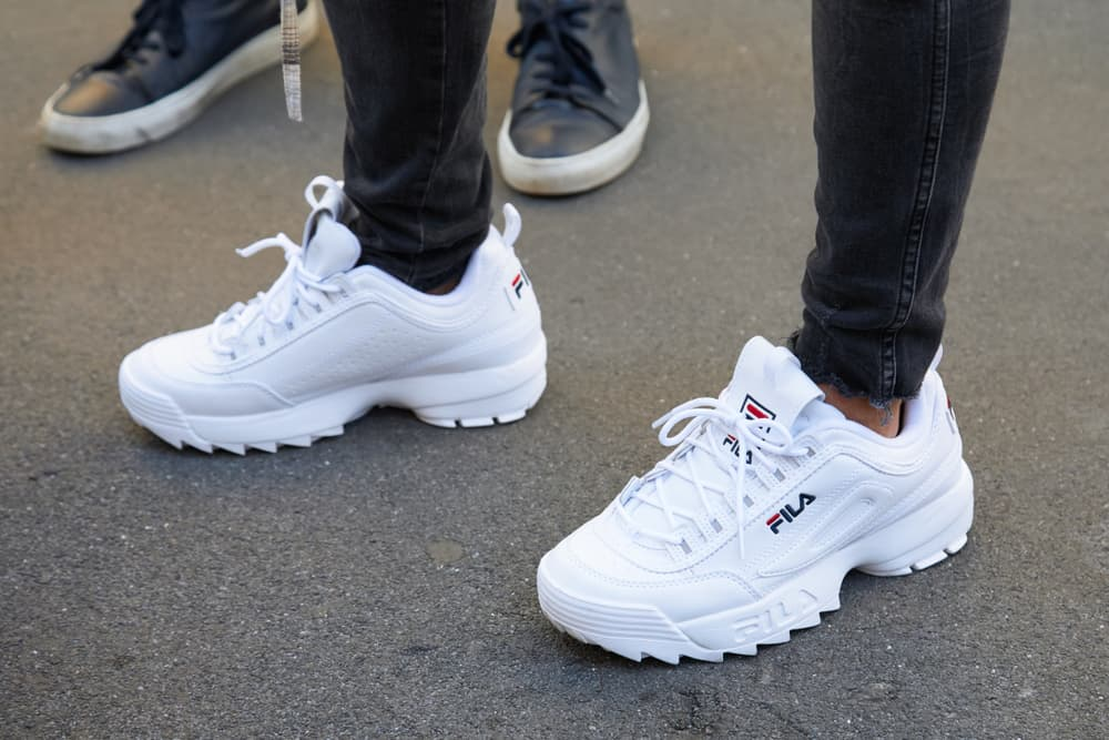 This is a close look at a man wearing a pair of chunky white Fila sneakers.