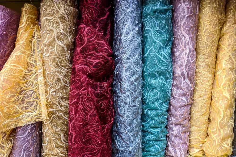 This is a close look at various colorful brocade fabrics on display.