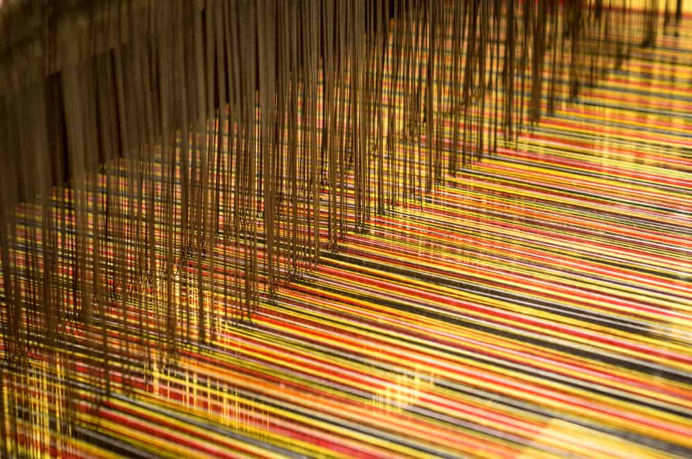 This is a close look at brocade fabric being weaved on a loom.