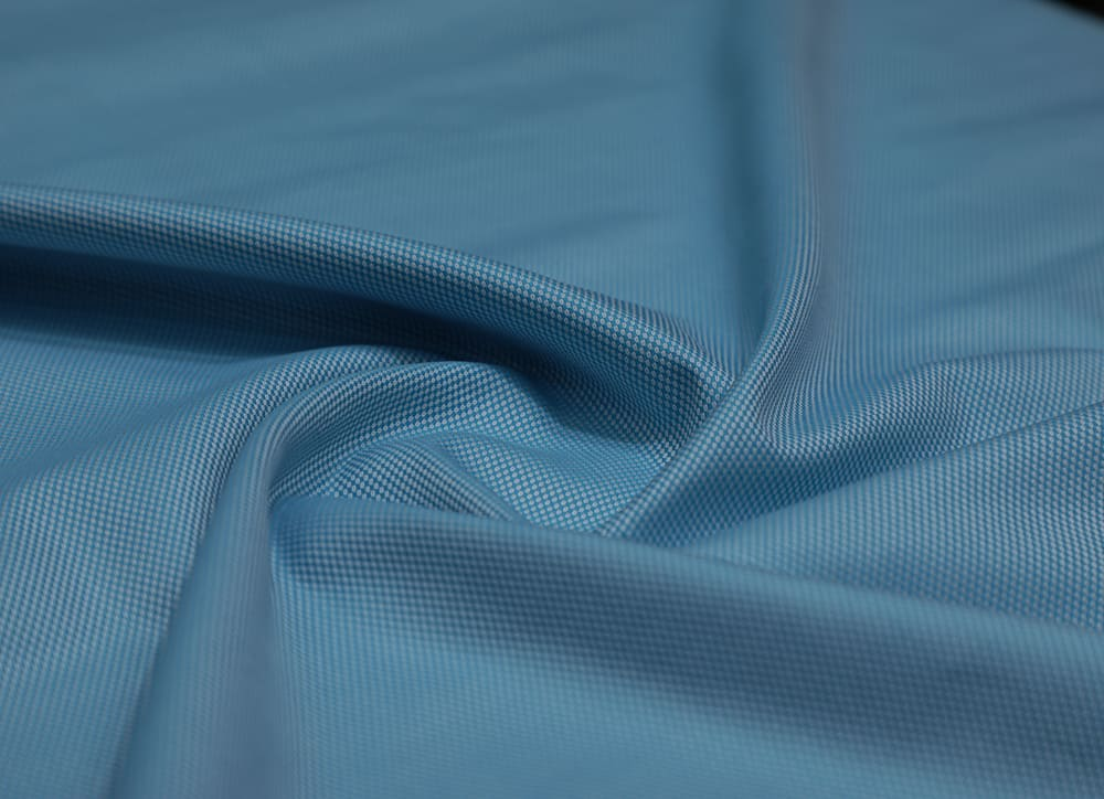 This is a close look at a piece of blue Poly Cotton fabric.