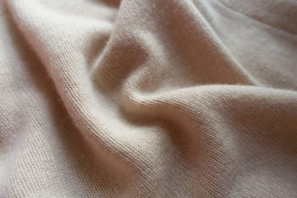 This is a close look at a beige wool fabric.