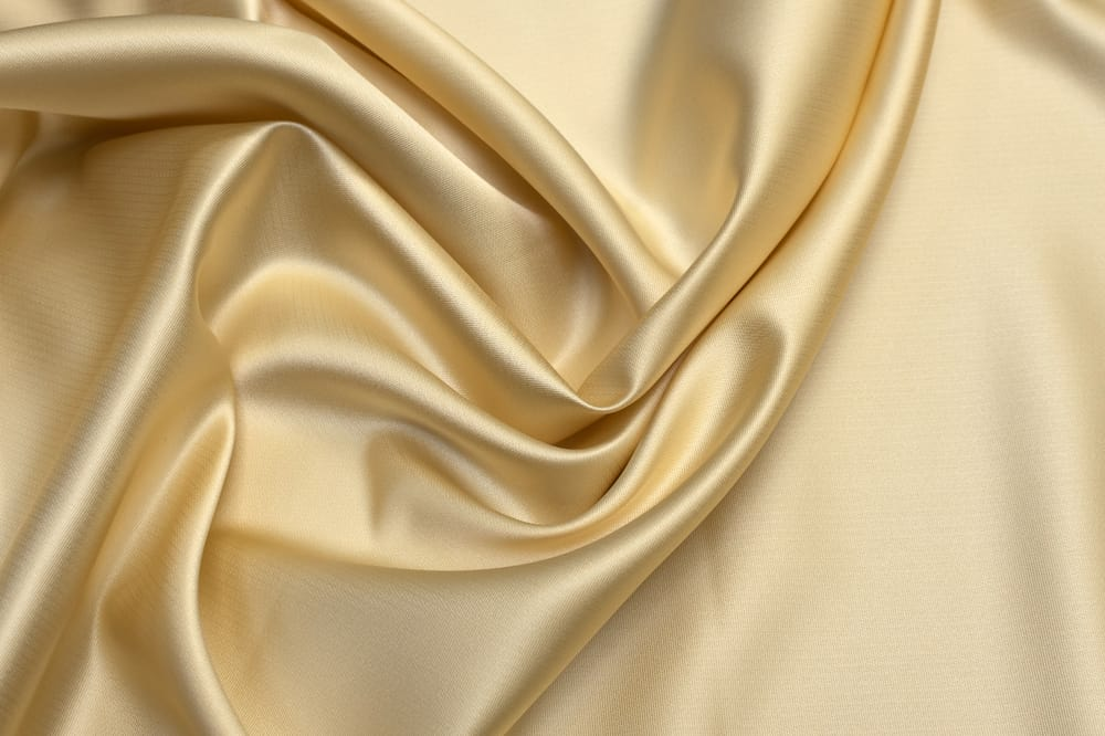 This is a close look at a silky Tafetta fabric with a golden hue.