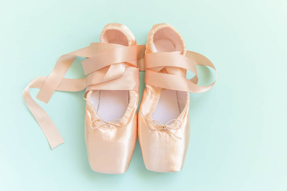 This is a close look at a pair of satin ballet shoes.
