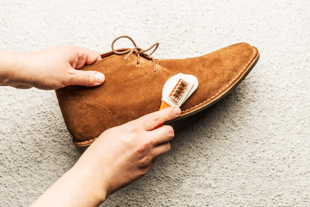 This is a close look at a man cleaning his Suede brown shoes.
