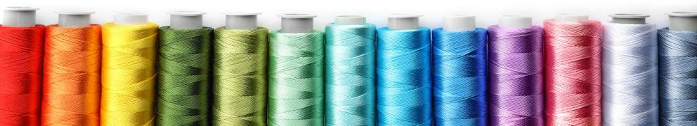 This is a close look at various colorful sewing threads.
