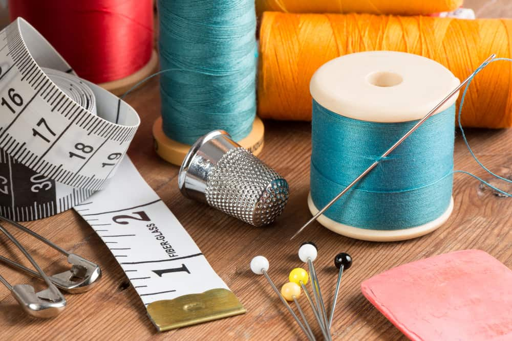 This is a close look at various sewing essentials on a wooden table.