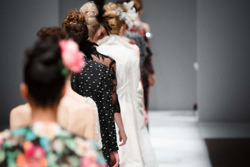 Models in various dresses walk the runway.
