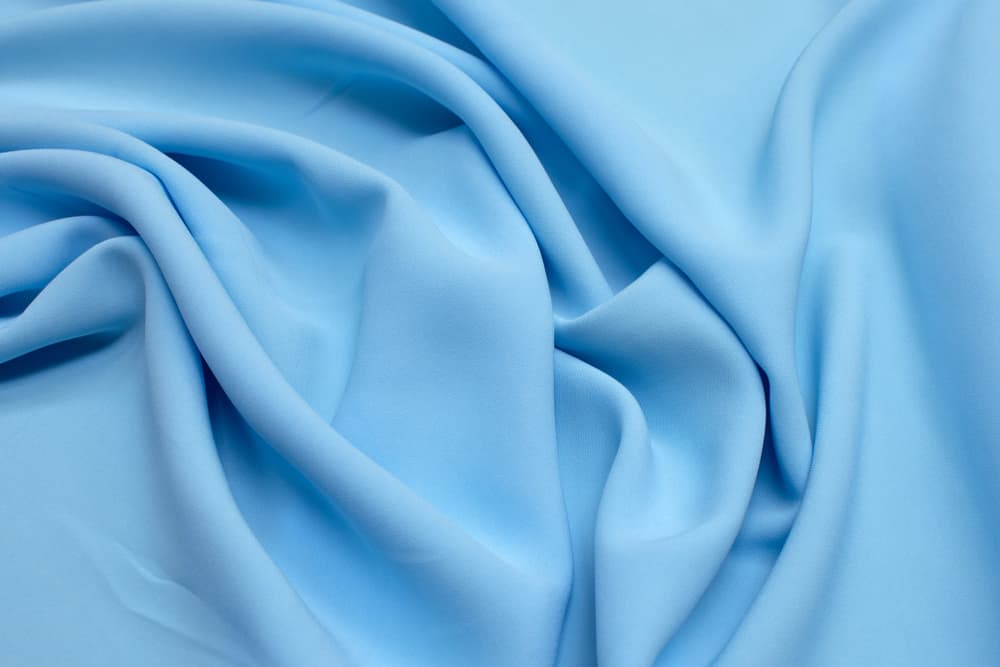 This is a close look at a piece of blue wrinkled rayon fabric.
