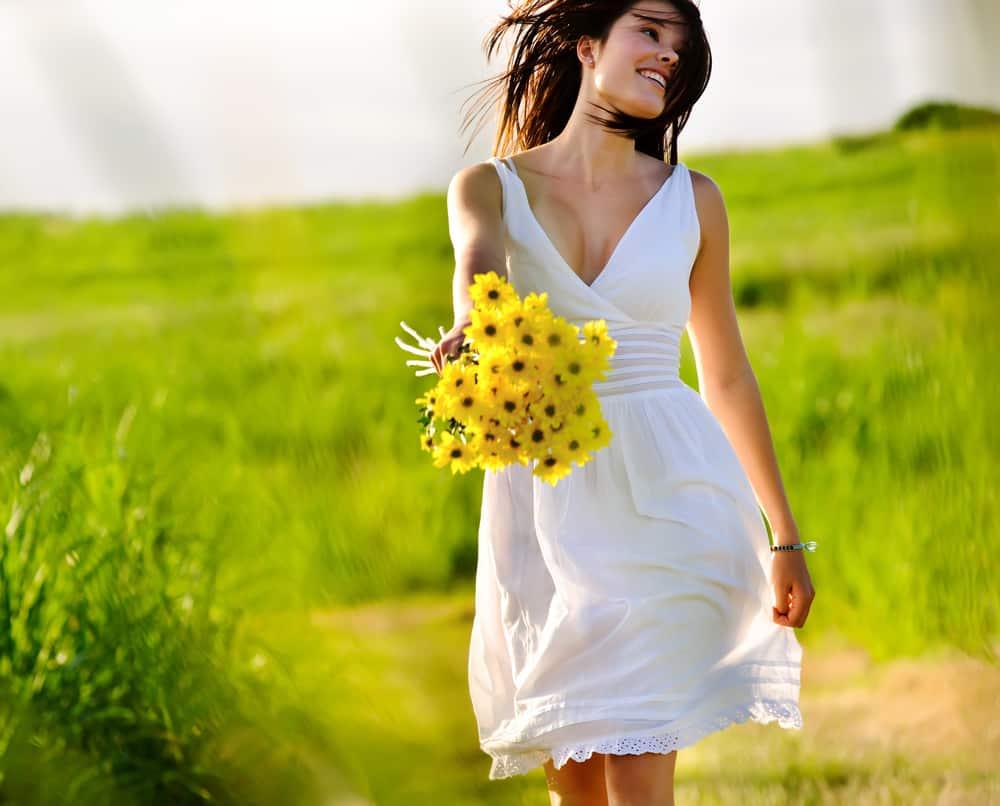 A woman wearing a white summer dress walking at a field of grass.
