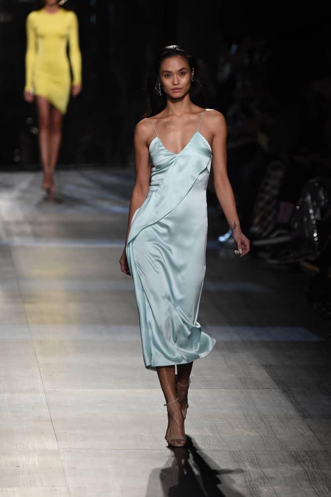 A model walking the runway wearing a blue silky Slip Dress.