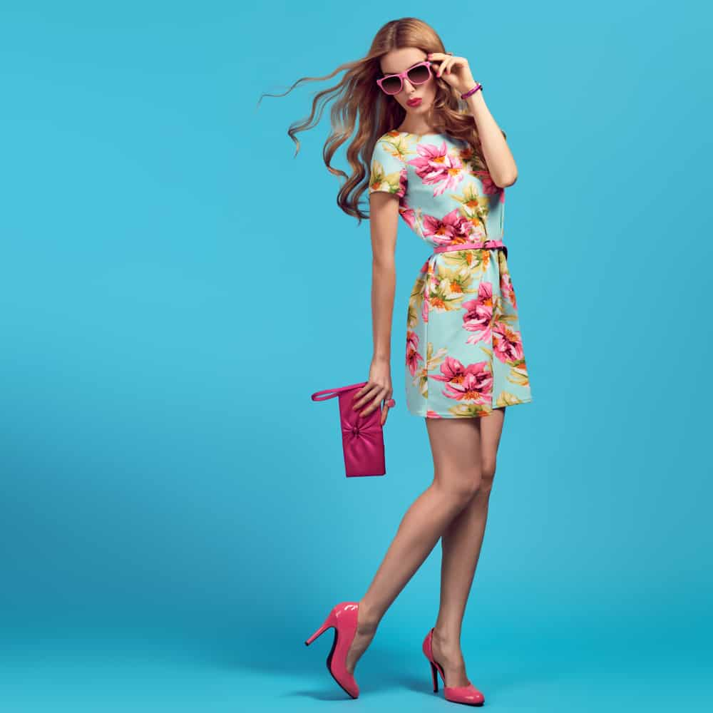 This is a woman wearing a colorful floral summer dress with matching accessories.