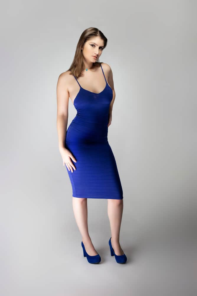 A woman wearing a sexy blue sleeveless dress paired with blue shoes.