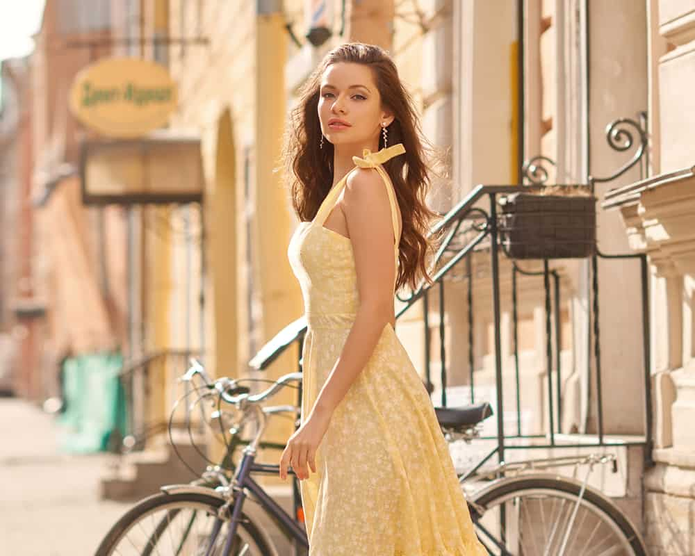This is a close look at a woman wearing a bright yellow Sundress.