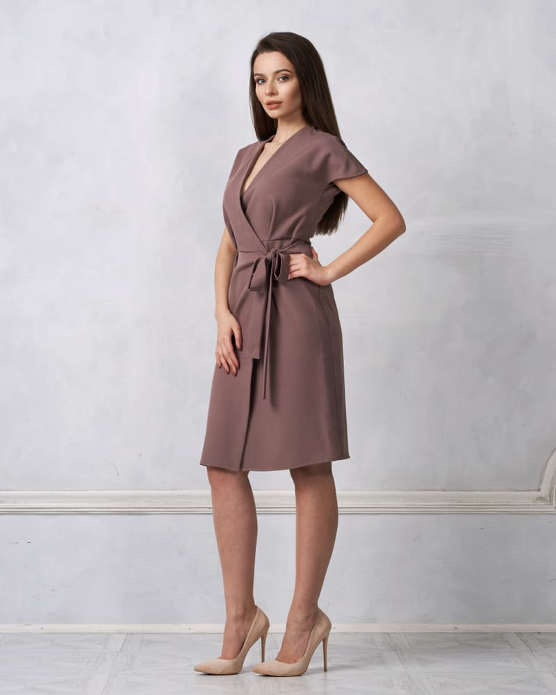 A woman wearing a brown Wrap Dress paired with heels.
