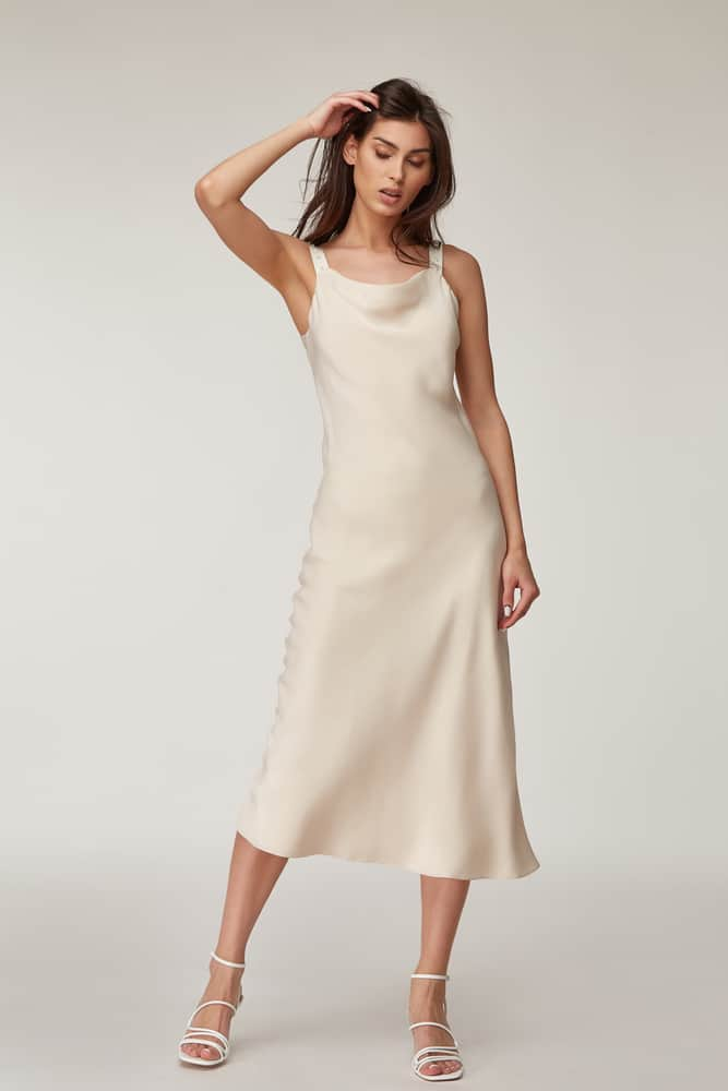 This is a woman wearing a silky beige Midi Dress.