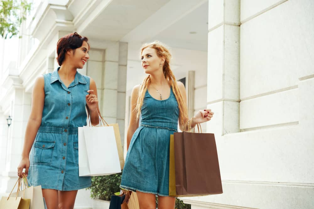 A couple of women walking while wearing denim dresses.