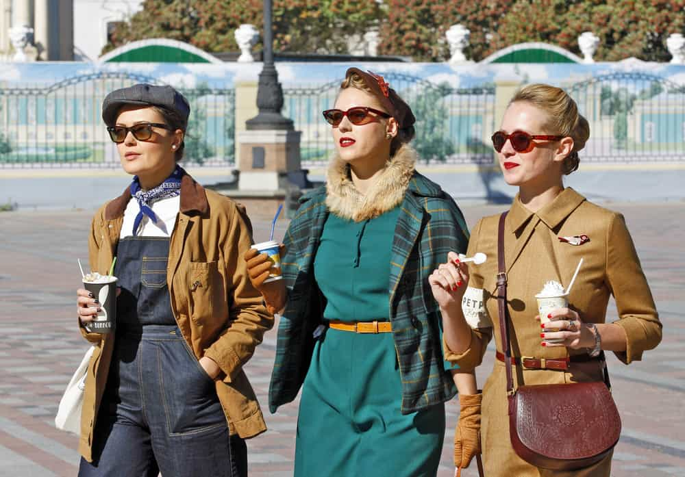 Women dressed in vintage clothes walking on the street.