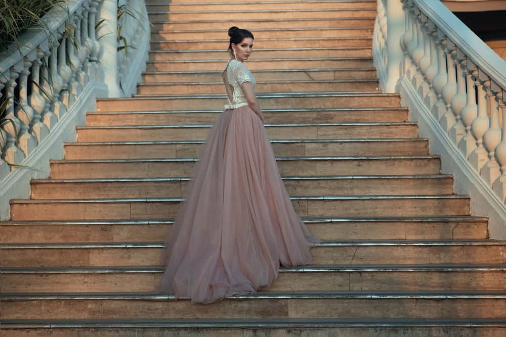 Woman in a ballroom dress walking up the stairs of a palace.