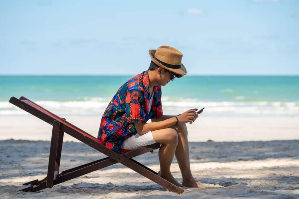 Man sitting on a wooden lounger near the beach.
