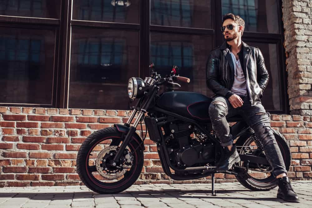Bearded man in leather jacket sitting on his bike.