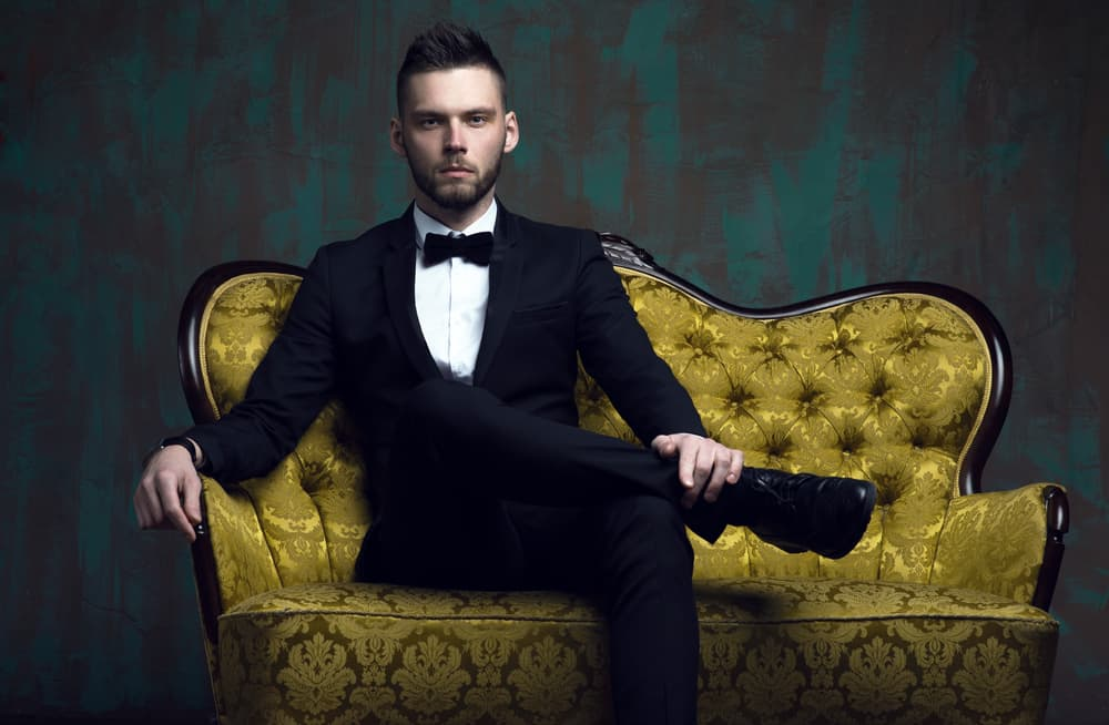 Man in his tuxedo sitting on a classy couch.