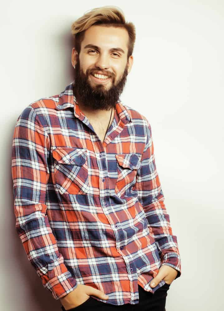 Bearded man wearing a checkered long sleeves polo.