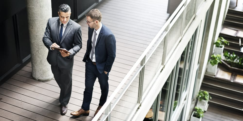 Two businessmen having discussion on the second-level balcony.