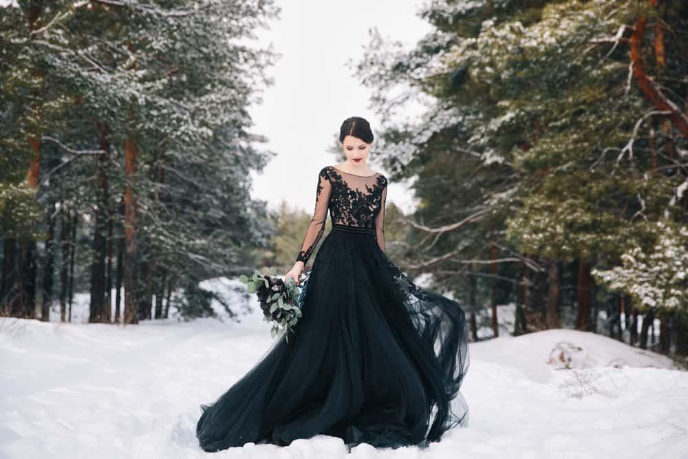 A bride wearing a black wedding dress in a wintry forest.