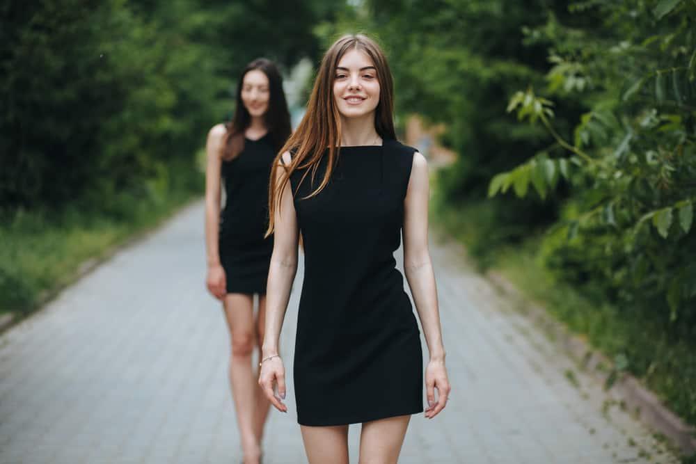 A couple of women walking down the street wearing little black dresses.