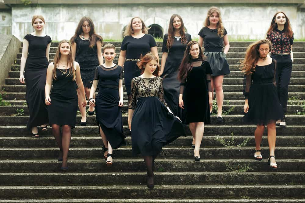 A group of women walking down the steps wearing black dresses.