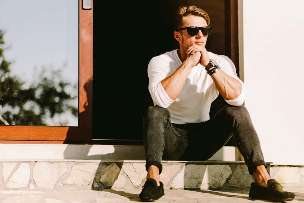 Man in casual outfit and shades sitting outside his house.